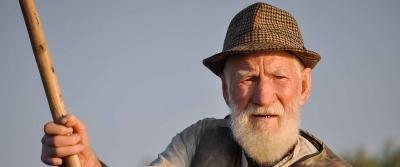 man wearing hat holding wooden rod under gray sky