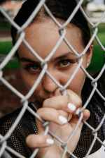 close up portrait photo of woman leaning on chain link fence